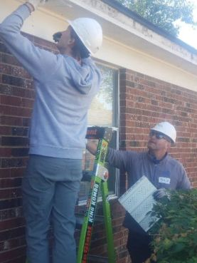 BC Cole placing soffit on house